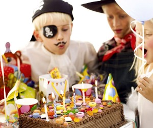 Children (6-10) Wearing Costumes and Blowing Out Candles on Birthday Cake